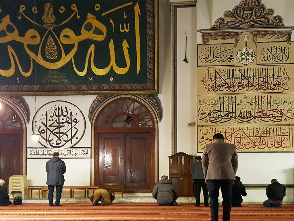 People are praying in grand mosque of bursa